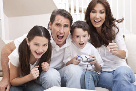 Happy family, parents, son and daughter, having fun playing video console games together, the young boy has the handset controller everyone else is cheering. photo