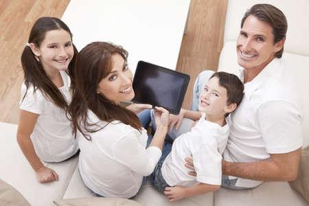 wealthy lifestyle: Una famiglia felice, attraente della madre, padre, figlio e figlia, seduto su un divano a casa di divertirsi usando un tablet PC