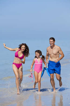 A happy family of mother, father and child, a daughter, running holding hands and having fun in the waves of a sunny beach photo