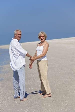 Feliz el senior pareja hombre y mujer junto tomados de la mano y caminar en una playa desierta tropical con cielo azul brillante