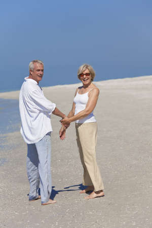Happy senior man and woman couple together holding hands and walking on a deserted tropical beach with bright clear blue sky photo