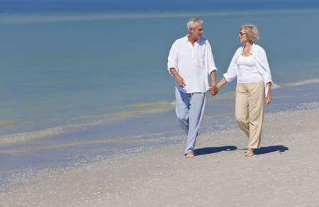 pareja de esposos: Feliz el senior pareja hombre y mujer junto tomados de la mano y caminar en una playa desierta tropical  Foto de archivo