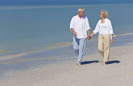 married couples: Happy senior man and woman couple together holding hands and walking on a deserted tropical beach