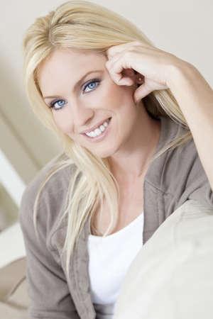 blonde yeux bleus: Natural portrait lumi�re d'une belle femme blonde aux yeux bleus se reposant sur son canap� � la maison