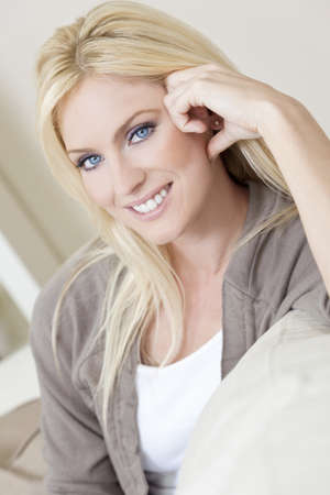 natural light: Retrato de luz natural de una hermosa mujer rubia con ojos azules, descansando en su sof� en casa