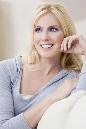 blonde yeux bleus: Portrait d'une belle femme blonde aux yeux bleus d'implantation � la maison sur un sofa ou canap�