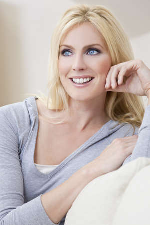 settee: Portrait of a beautiful blond woman with blue eyes siting at home on a sofa or settee