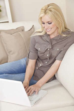 settee: Beautiful young woman at home sitting on sofa or settee using her laptop computer and smiling