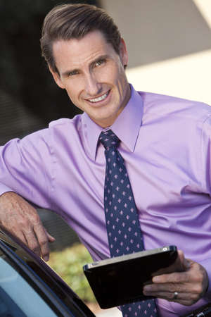 A smart successful businessman outside using a tablet computer