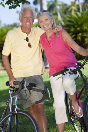Happy senior man and woman couple together cycling on bicycles outside in a sunny green park photo
