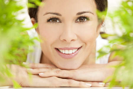 Health spa nature concept studio portrait of a beautiful young woman or girl resting on her hands smiling through natural green leaves photo