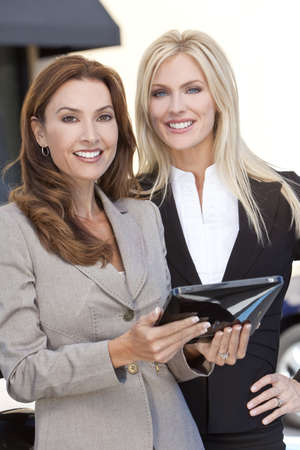 Two smart women in business or businesswomen outside using a tablet computer or iPad photo