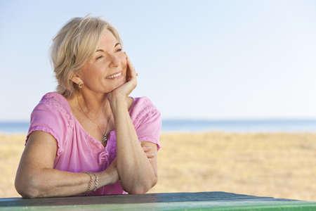 mujer pensando: Una atractiva mujer senior elegante y feliz sentado fuera fuera de una tabla y pensando, detr�s de ella es una playa y el mar Foto de archivo