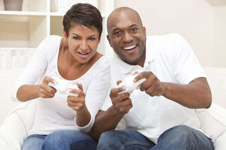 sexes: African American couple, man and woman, having fun playing video console games together.  Stock Photo