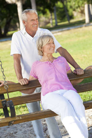 Happy senior man and woman couple together outside in sunshine on a park swing photo