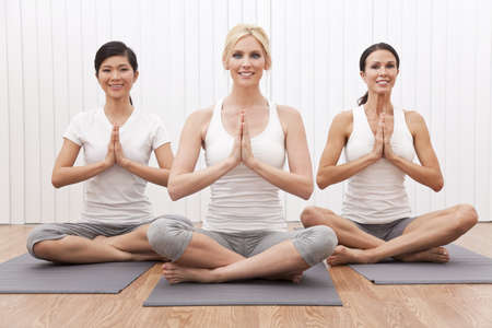 mats: An interracial group of three beautiful young women sitting cross legged in a yoga position at a gym