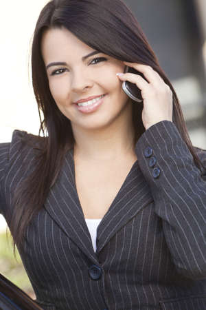 Outdoor portrait of a beautiful young Latina Hispanic woman or businesswoman smiling and using her cell mobile phone photo