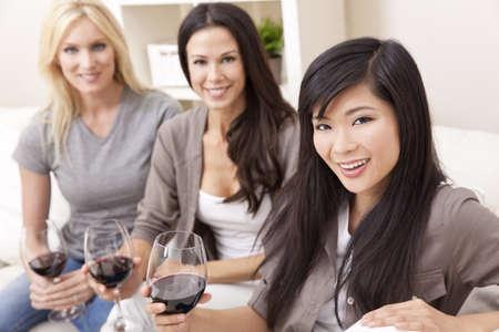jovenes tomando alcohol: Grupo interracial de tres hermosas mujeres j�venes amigos en casa beber vino tinto juntos Foto de archivo