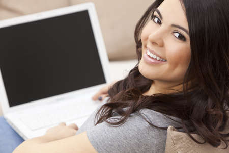 using computer: Beautiful happy young Latina Hispanic woman smiling and using a laptop computer at home on her sofa