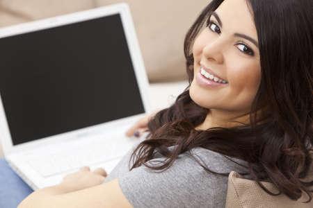 usando computadora: Hermosa feliz Hispano Latina joven sonriente y con un equipo port�til en casa en su sof� Foto de archivo