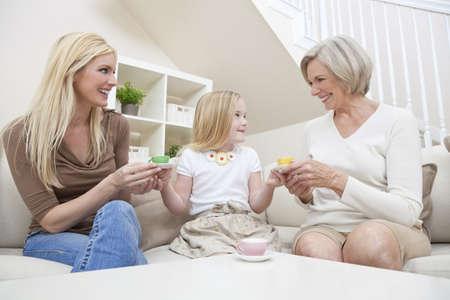 family one: Tre generazioni di donne di una famiglia a casa. Madre, la nonna e la figlia che sta giocando a servire il t� in un servizio da t� di porcellana.