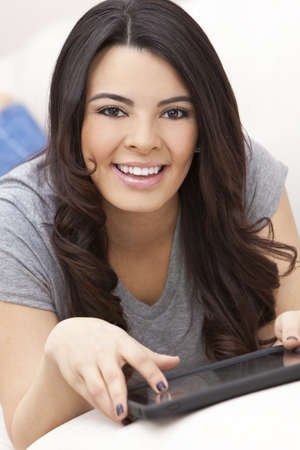 Beautiful happy young Latina Hispanic woman smiling, laying down and using a tablet computer at home on her sofa Stock Photo - 9952896