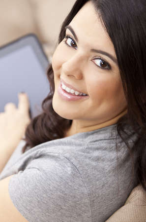 Beautiful happy young Latina Hispanic woman smiling and using a tablet computer at home on her sofa Stock Photo - 9952909