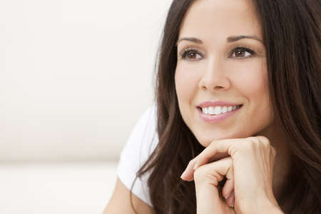 smiling teeth: Portrait of a beautiful brunette young woman with perfect teeth smiling and resting on her hands