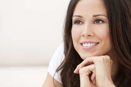 Portret van een mooie brunette jonge vrouw met perfecte tanden glimlachend en rusten op haar handen
