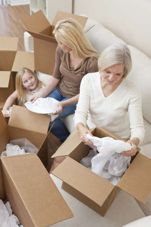 unpacking: Female generations of a family, mother, daughter & grandmother unpacking boxes and moving into a new home.