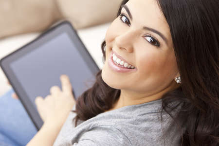 Beautiful happy young Latina Hispanic woman smiling and using a tablet computer at home on her sofa photo