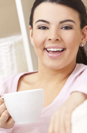 enigmatic: A beautiful young Latina Hispanic woman or girl with a wonderful enigmatic smile drinking tea or coffee from a white cup  Stock Photo