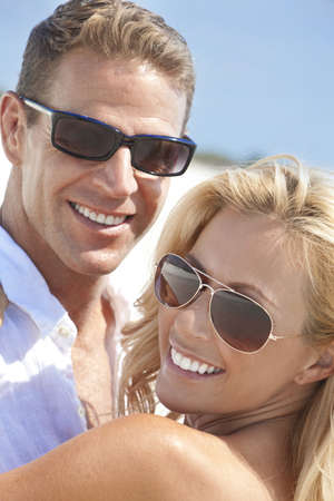 sexy couple on beach: A happy and attractive man and woman couple wearing sunglasses and smiling in sunshine at the beach
