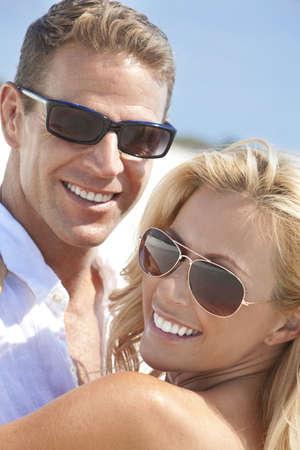 sunglasses: Un feliz y atractivo hombre y mujer par llevar gafas de sol y sonriendo en sol en la playa