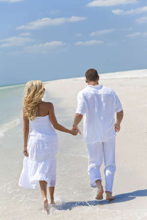 Happy young man and woman couple running or walking and holding hands on a deserted tropical beach with bright clear blue sky photo