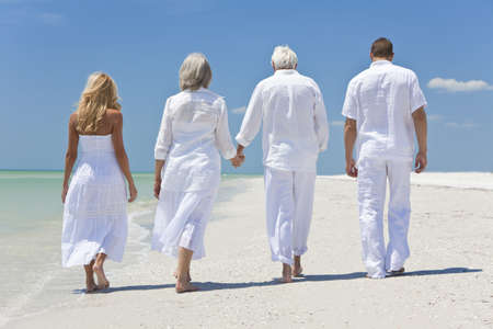 two generation family: Rear view of four people, two seniors, couples or family generations, holding hands, walking on a tropical beach Stock Photo