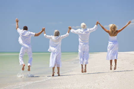 Rear view of four people, two seniors, couples or family generations, holding hands, having fun and jumping in celebration on a tropical beach Stock Photo - 9952911