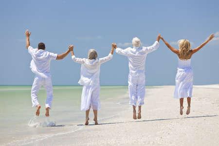 tercera edad: Vista posterior de cuatro personas, dos mayores, parejas o familias generaciones, tomados de la mano, divertirse y saltos en la celebraci�n en una playa tropical