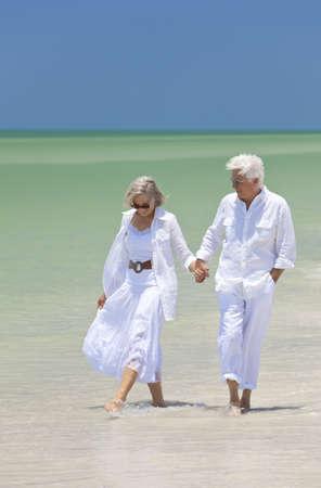 senioren wandelen: Gelukkige senior man en vrouw paar wandelen, glimlachend en hand in hand op een verlaten tropisch strand met helder heldere blauwe hemel