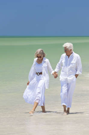 aging woman: Happy senior man and woman couple walking, smiling and holding hands on a deserted tropical beach with bright clear blue sky
