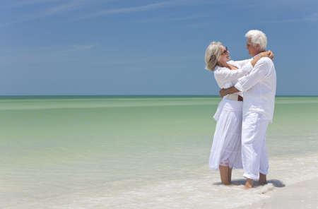 Happy senior man and woman embracing on a deserted tropical beach with bright clear blue sky photo