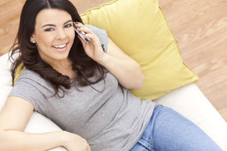 Beautiful happy young Latina Hispanic woman smiling and using her cell phone at home on her sofa photo