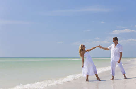 beach clothes: Happy young man and woman couple dancing and holding hands on a deserted tropical beach with bright clear blue sky