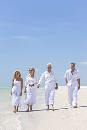 Four people, two seniors, couples or family generations, holding hands, having fun and walking on a tropical beach photo