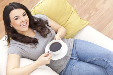 woman drinking coffee: A beautiful young Latina Hispanic woman or girl with a wonderful toothy smile drinking black tea or coffee from a white cup at home