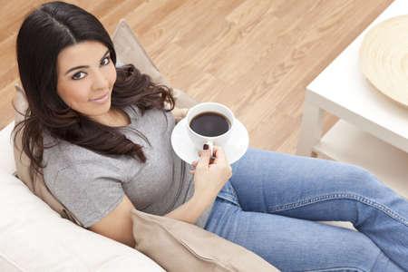 enigmatic: Una bella giovane donna Latina Ispanici o ragazza con un sorriso enigmatico meraviglioso bere t� o caff� da una tazza bianca a casa sul suo divano