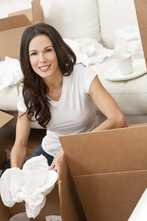 A beautiful single young woman unpacking boxes and moving into a new home. Stock Photo - 9952903