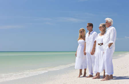 two couples: Two couples, generations of a family together holding hands on a tropical beach Stock Photo