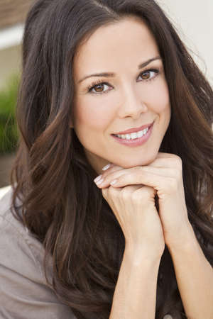 Portrait of a beautiful brunette young woman with perfect teeth smiling and resting on her hands photo