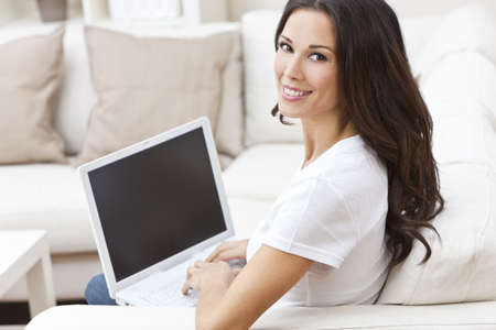 Beautiful young brunette woman at home sitting on sofa or settee using her laptop computer and smiling photo